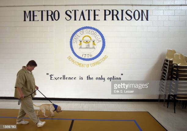 Georgia prison inmate Stephanie Walker works with her Labrador retriever puppy Gage during guide dog training at Metro State Prison August 27 2002 in...
