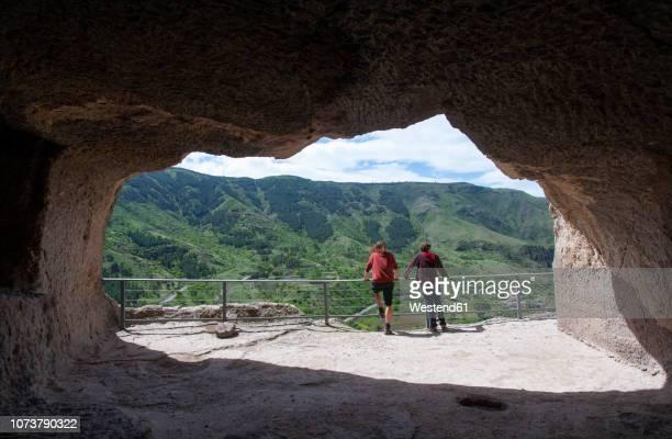 georgia, samtskhe-javakheti, tourists at cave city vardzia - georgia stock-fotos und bilder
