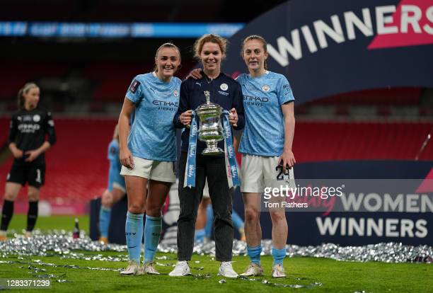 Georgia Stanway, Aoife Mannion, and Keira Walsh of Manchester City celebrate with the Vitality Women's FA Cup Trophy following their team's victory...