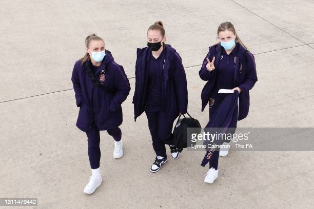 Georgia Stanway, Keira Walsh and Leah Williamson of England walk to board the plane as the England Women's Senior Squad travel to France for their...