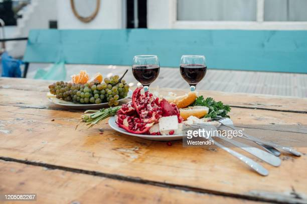 georgia, tbilisi, fresh fruit and glasses of red wine on wooden table outdoors - georgia country stock pictures, royalty-free photos & images