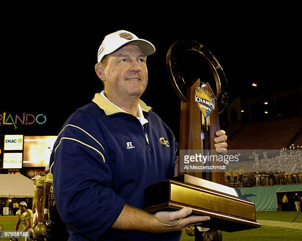Georgia Tech coach Chan Gailey holds the championship trophy at the Champs Sports Bowl game Dec 21 2004 in Orlando Florida Georgia Tech defeated...