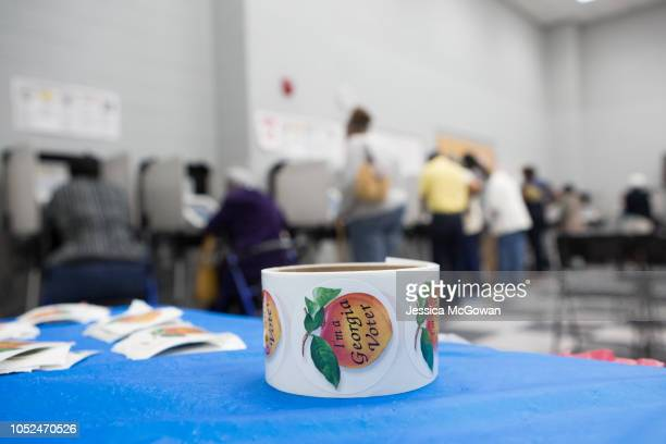 Georgia voter stickers lay on a table while people cast ballots at CT Martin Natatorium and Recreation Center on October 18 2018 in Atlanta Georgia...