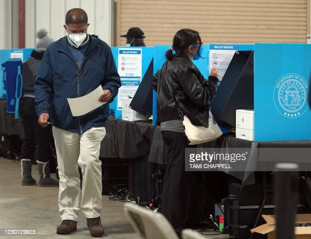 Georgia voters mark their ballots during the first day of early voting in the US Senate runoffs at the Gwinnett County Fairgrounds, December 14 in...