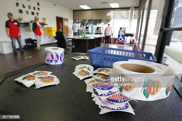 Georgia voting stickers sit atop an extra voting machine as a voter places her vote during the US presidential election at the AthensClarke County...