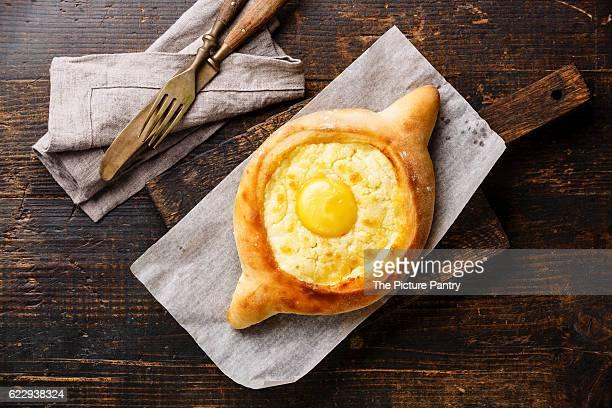 Georgian cheese pastry Ajarian khachapuri on wooden cutting board
