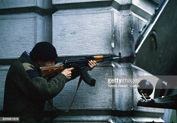 A Georgian man aims his AK47 from behind a building in the streets of Tbilisi Georgia where a civil war has been going on since shortly after the...