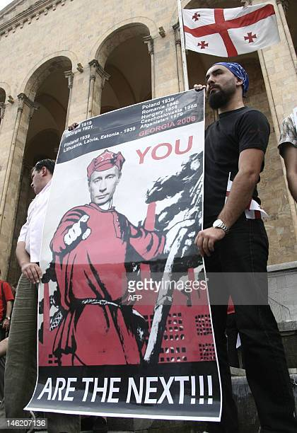 Georgian men hold a poster of Russian Prime Minister Vladimir Putin rally in front of the parliament building in central Tbilisi on August 12 2008 to...