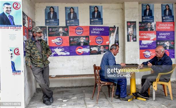 Georgian men play dominoes at a bus stop pasted over with presidential candidates preelection posters in Telavi on October 19 2018 The presidential...