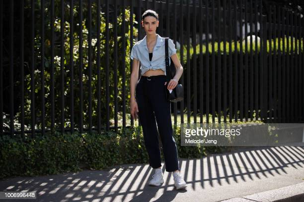 Georgian model Tatia Akhalaia wears a blue shirt black pants a black purse and white sneakers after the Ulyana Sergeenko show during Couture...