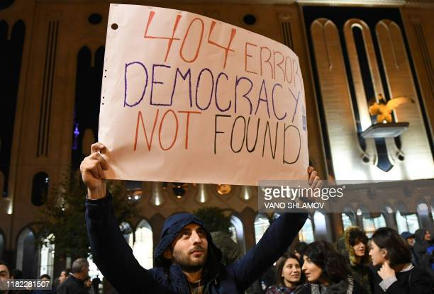 A Georgian opposition supporter hold poster during rally outside the parliament in central Tbilisi on November 14 2019 Thousands of opposition...