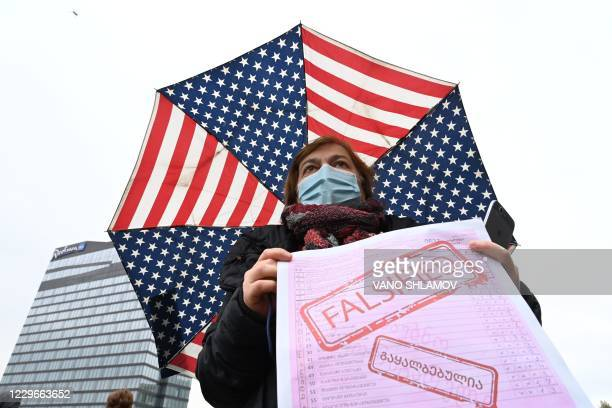 Georgian opposition supporter holds a poster and an umbrella in the colours of the US flag as she attends a rally in central Tbilisi on November 18,...