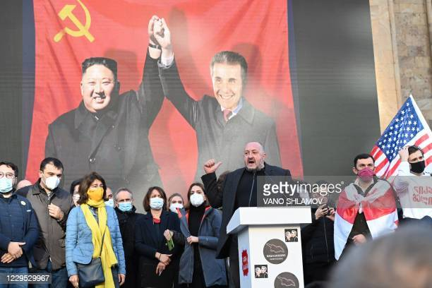 Georgian opposition supporters attend a rally next to a banner showing Georgian ruling Georgian Dream party leader, billionaire and former prime...