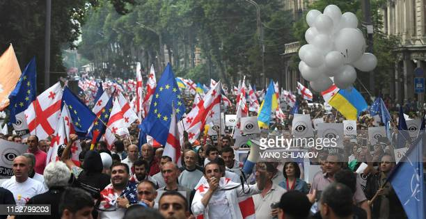 Georgian opposition suppporters take part in a march demanding the resignation of Interior Minister Giorgi Gakharia whom they accuse of using...