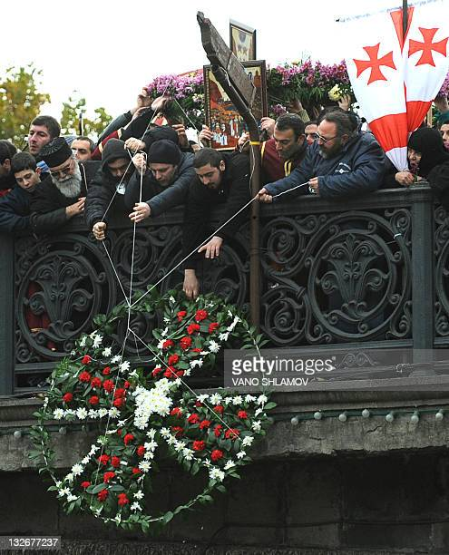 Georgian Orthodox believers lay a wreath on a bridge over the Kura river during a procession in central Tbilisi on November 13 during an annual...