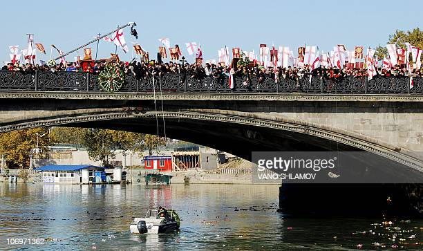 Georgian orthodox believers put wreaths into the Kura River during a religious procession devoted to the dead in central Tbilisi on November 13 2010...
