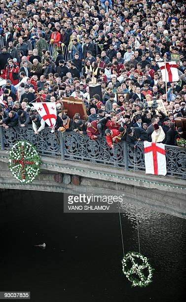 Georgian orthodox believers put wreaths into the Kura River during a religious procession devoted to the dead in central Tbilisi on November 13 2009...