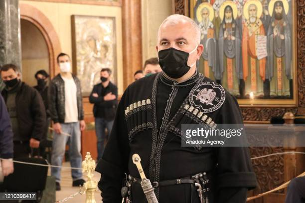 Georgian Orthodox believers wearing face mask as a preventive measure against coronavirus attend a Easter service at Holy Trinity Cathedral of...
