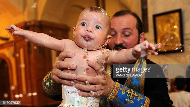 Georgian Orthodox priest baptises a baby during a mass baptism ceremony at the Holy Trinity Cathedral in Tbilisi on July 13 2016 / AFP / Vano Shlamov