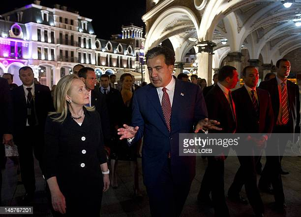 Georgian President Mikheil Saakashvili talks with US Secretary of State Hillary Clinton as they leave following a cultural dancing and singing...