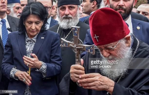 Georgian President Salome Zurabishvili and Georgian Orthodox Patriarch Ilia II take part in a prayer during rally to commemorate the 30th anniversary...