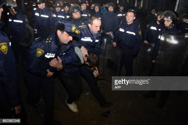Georgian riot police officers detain a protester early on March 12 2017 in Georgia's Black Sea port of Batumi during clashes reportedly following a...