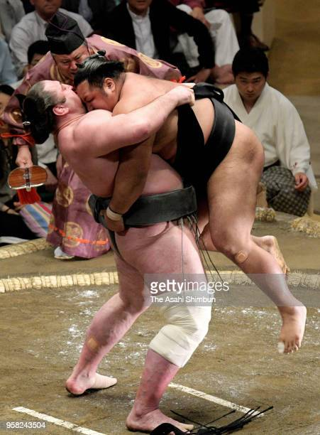 Georgian sekiwake Tochinoshin lifts Shohozan during their bout on day one of the Grand Sumo Summer Tournament at Ryogoku Kokugikan on May 13 2018 in...