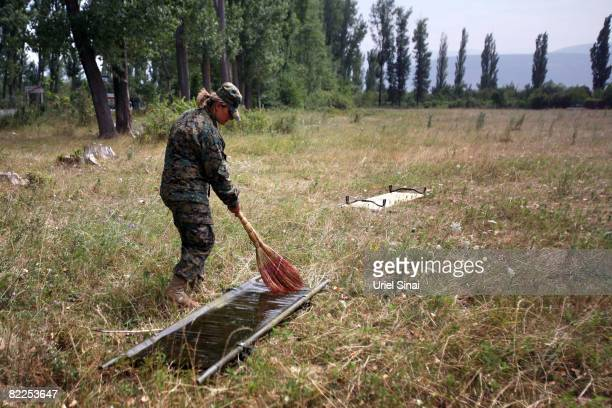 A Georgian soldier cleans a stretcher on the road between Tskinvali and Gori 20 km from the South Ossetian border on August 2008 near Gori Georgia...