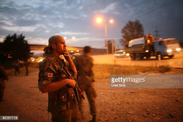 A Georgian soldier smokes as Georgian soldiers head towards Tbilisi on August 11 2008 just outside Gori Georgia Russia called today for Georgian...