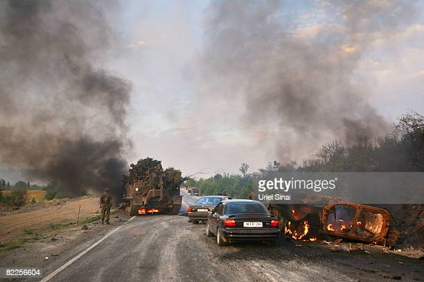 A Georgian soldier walks away from a burning armoured vehicle on the road to Tbilisi on August 11 2008 outside Gori Georgia Russia called today for...