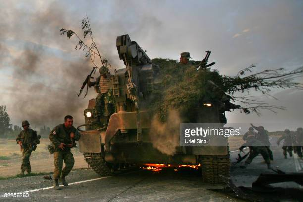 Georgian soldiers escape their burning armoured vehicle on the road to Tbilisi on August 11 2008 just outside Gori Georgia Russia called today for...