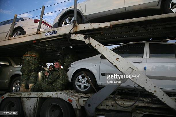 Georgian soldiers head towards Tbilisi on top of a vehicle carrier on August 11 2008 just outside Gori Georgia Russia called today for Georgian...