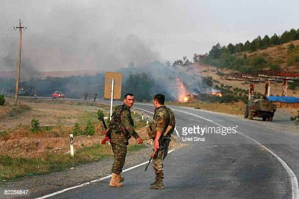 Georgian soldiers walk from the scene of a destroyed armoured vehicle on the road to Tbilisi on August 11 2008 just outside Gori Georgia Russia...
