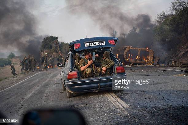 Georgian troops ride in a civilian vehicle as a Georgian Armoured Personel Carrier lies wrecked on the road between Gori and Tibilisi on August 11...