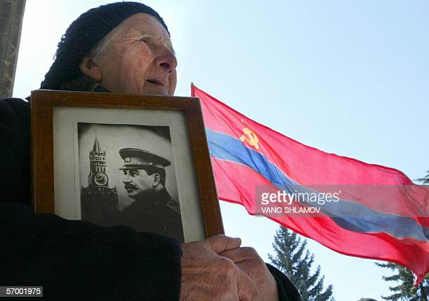 Georgian woman holds a portrait of former Soviet dictator Joseph Stalin commemorating the 53rd anniversary of his death in the Georgian town of Gori...