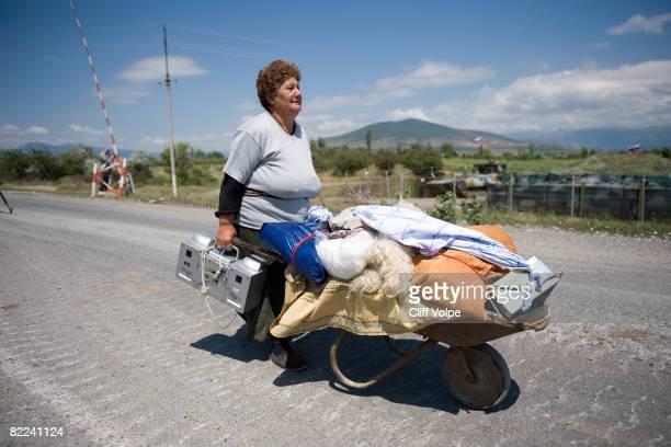 Georgian woman pushes her belongings in a wheelbarrow along the road from Tskinvali to Gori on August 10 2008 near Gori Georgia After calling a...