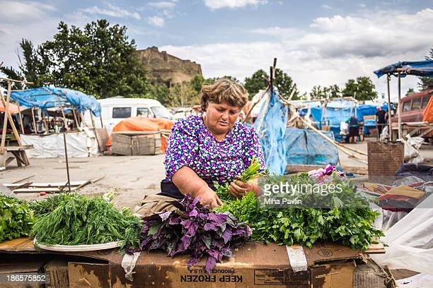CONTENT] Georgian woman wearing bright pink shirt selling fresh herbs on Sunday open air market in Gori Georgia Caucasus