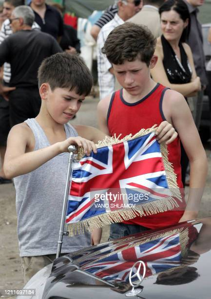Georgians from the South Ossetia conflict zone examine the British flag on an official car on August 20 2008 in a refugee camp outside Tbilisi during...