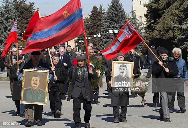 Georgians hold portraits of former Soviet dictator Joseph Stalin commemorating the 53rd anniversary of his death in the Georgian town of Gori some 80...