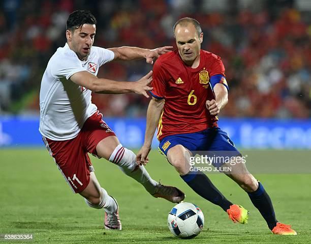 Georgia's forward Giorgi Chanturia vies for the ball with Spain's midfielder Andres Iniesta during the EURO 2016 friendly football match Spain vs...