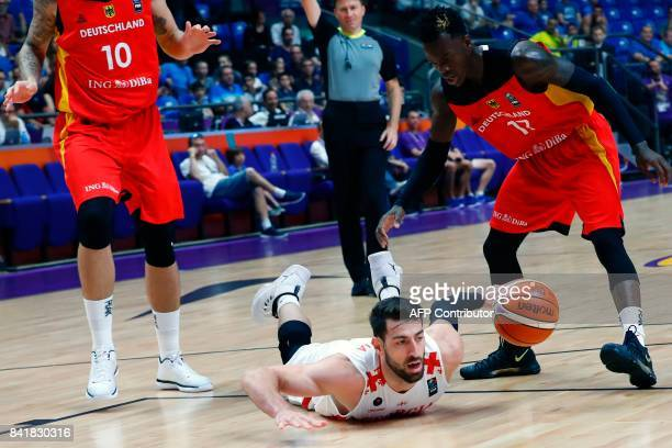 Georgia's forward Tornike Shengelia falls as he vies for the ball with Germany's point guard Dennis Schroder and power forward Daniel Theis during...