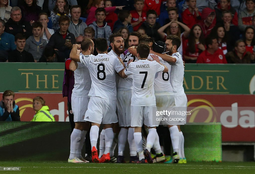 Georgia's midfielder Tornike Okriashvili is mobbed by teammates after scoring his team's first goal during the World Cup 2018 football qualification match between Wales and Georgia at Cardiff City Stadium in Cardiff, south Wales on October 9, 2016. / AFP / Geoff CADDICK