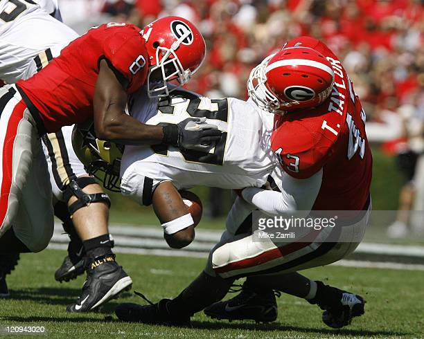 Georgia's Paul Oliver and Tony Taylor tackle Vanderbilt tailback Cakssen Jackson-Garrison at Sanford Stadium in Athens, Georgia, October 14, 2006.