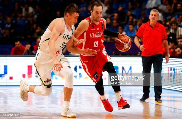 Georgia's shooting guard Duda Sanadze dribbles as he is marked by to score as he is marked by Lithuania's small forward Edgaras Ulanovas during the...