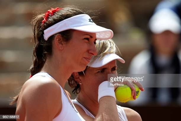 Georgina Garcia Perez and Maria Jose Martinez of Spain talk in their doubles match against Montserrat Gonzalez and Veronica Cepede of Paraguay during...