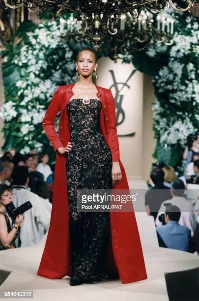 Georgina Robertson en robe de dentelle noir et manteau rouge défile pour la collection Saint Laurent Haute Couture AutomneHiver 97/98 le 9 juillet...
