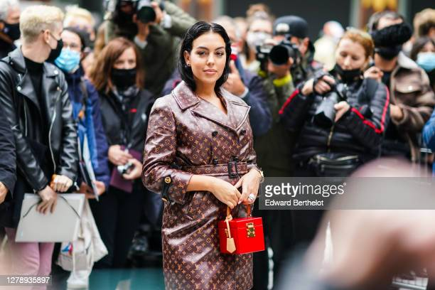 Georgina Rodriguez wears a brown leather Vuitton monogram print trench coat, a red rigid box bag, outside Louis Vuitton, during Paris Fashion Week -...