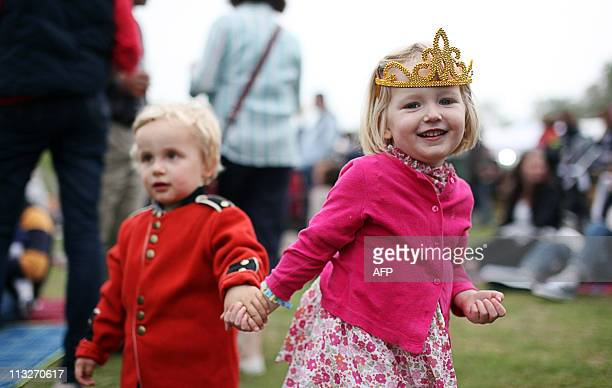 Georgina Wallace right and Alfie Stevenson left celebrate the royal wedding at a Tea in the Park event in the Middleton's home village of Bucklebury...