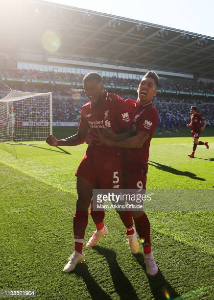 Georginio Wijnaldum of Liverpool celebrates scoring their first goal with Roberto Firmino during the Premier League match between Cardiff City and...