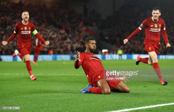 Georginio Wijnaldum of Liverpool celebrates with Jordan Henderson and Andy Robertson after scoring his team's first goal during the UEFA Champions...
